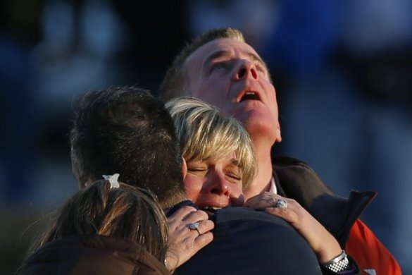 The families of victims grieve near Sandy Hook Elementary School, where a gunman opened fire on school children and staff in Newtown, Connecticut on December 14, 2012. (Yahoo.com)