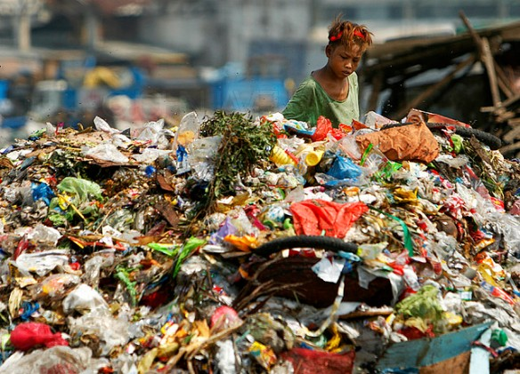 A young scavenger collect recyclable items from a garbage dump site. This photo is a symbol of non-ending story of poverty in our country.