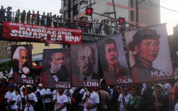 Kilusang Mayo Uno (KMU) protesters waving posters with photos of Karl Marx, Friedrich Engels, Vladimir Lenin, Joseph Stalin, and Mao Zedong.